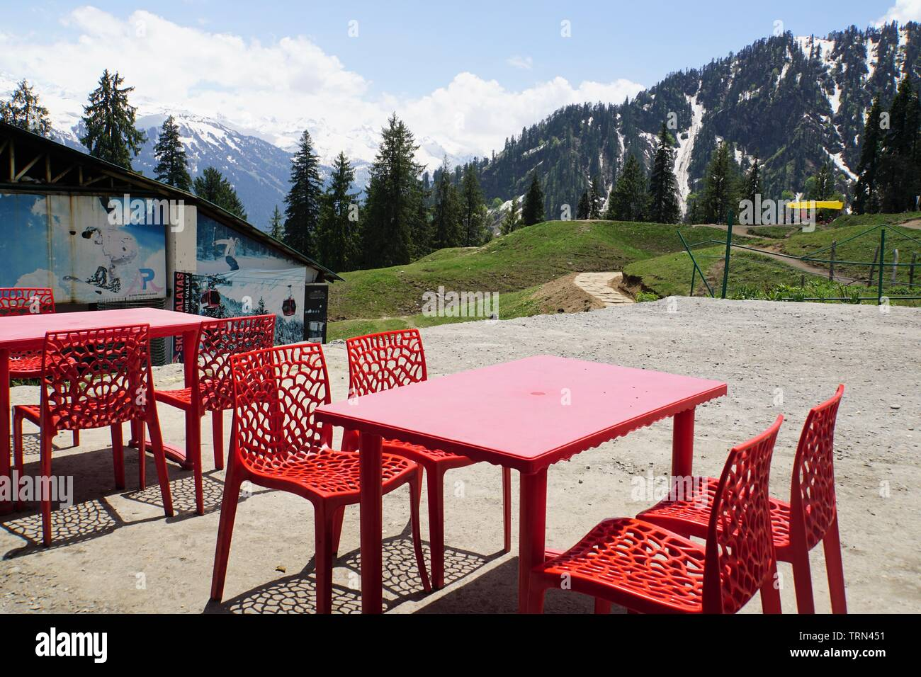 Red Tables and Chairs with a Scenic View of the Himalayas - Stock Image