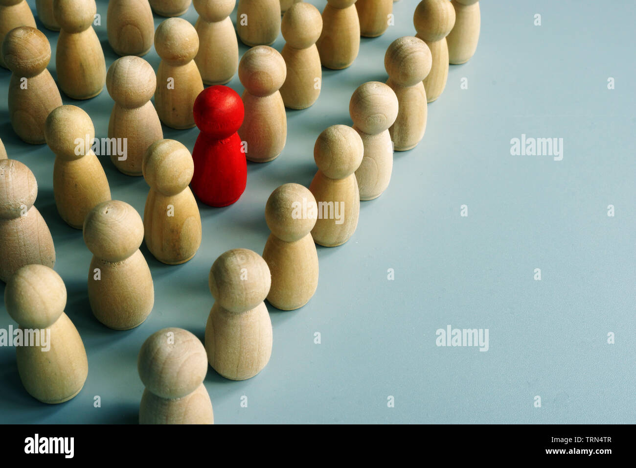 Unique red figurine stand out in the crowd from wooden ones. Stock Photo