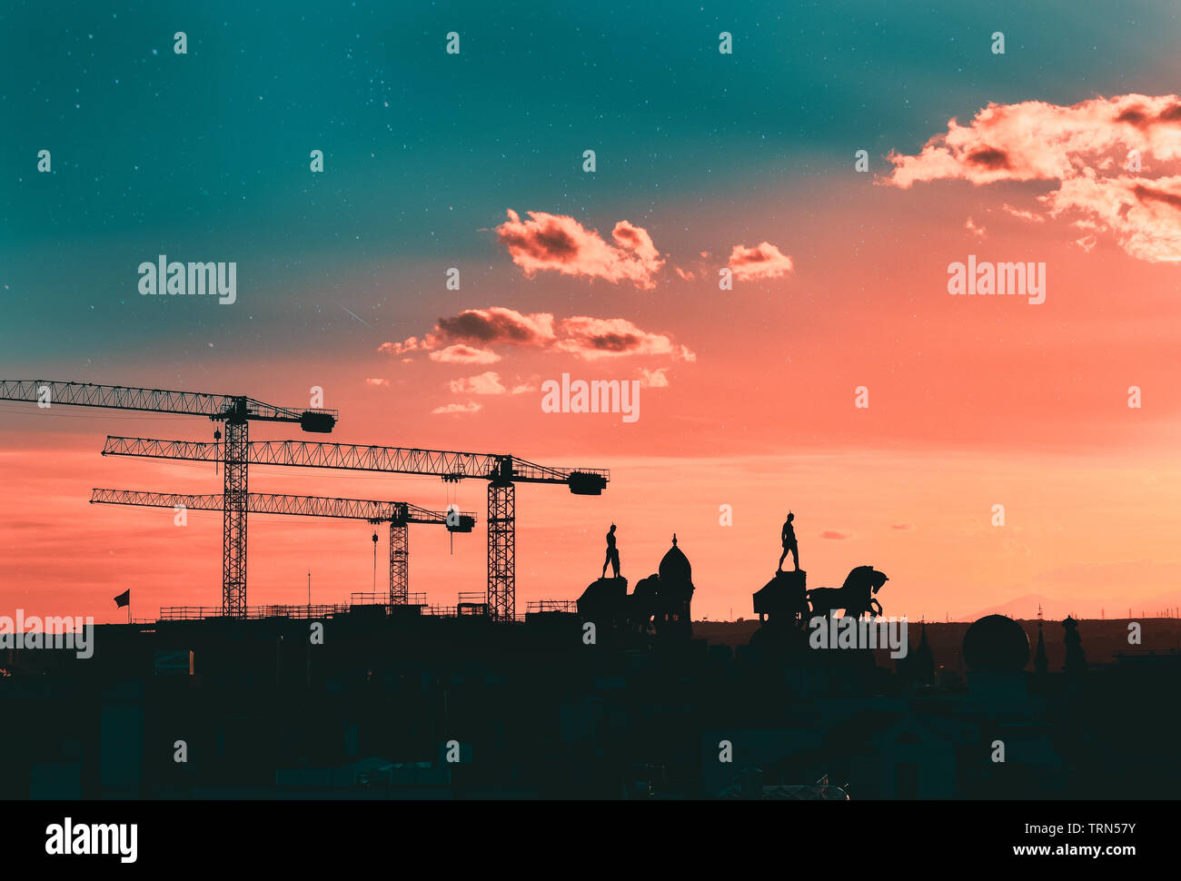 Silhouettes of cranes, statues and buildings of madrid, with a creative star sky of coral and teal color. Madrid, Spain - Stock Image