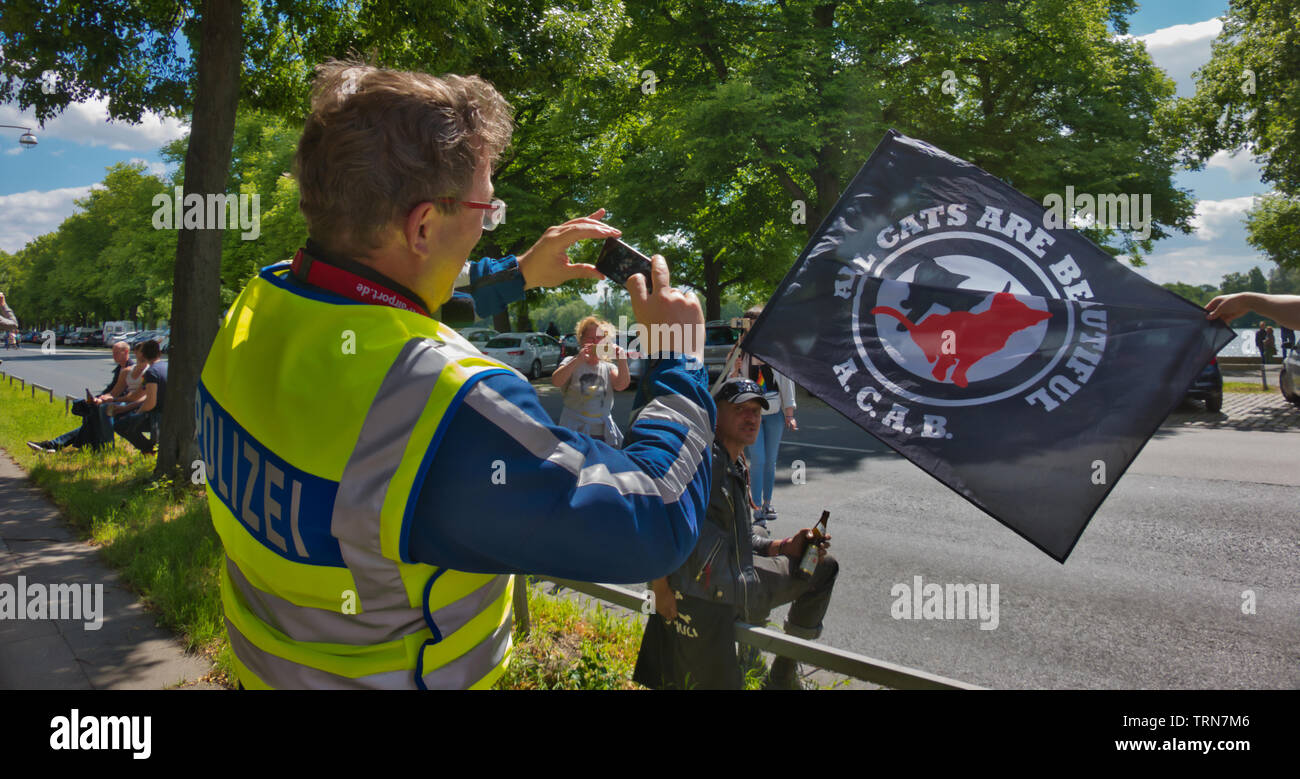 Hannover, Germany, June 8., 2019: German policeman photographing a demonstrator at the edge of a demonstration with flag with the inscription ACAB, Al - Stock Image