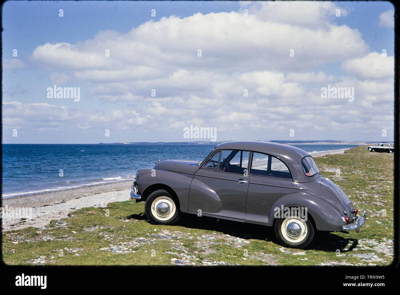 Morris Minor parked on the seafront, Traeth Llanddwyn, Anglesey, North Wales, 1962. View with Llanddwyn Bay beyond and Llanddwyn Island in the distance. - Stock Image