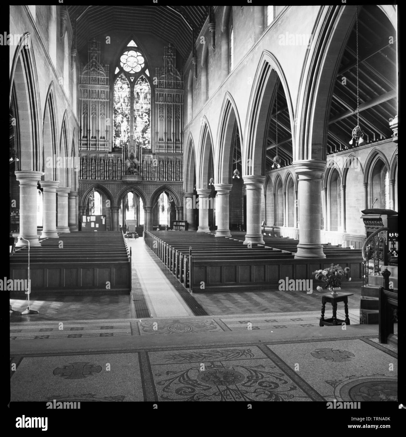 St George's Church, St George's Close, Jesmond, Newcastle upon Tyne, c1955-c1980. An interior view of the chancel in St George's Church, showing the nave and west wall, traceried with Caen stone and with a statue of St George. Completed in 1888, the church was designed by TR Spence, and commissioned by Charles Mitchell. The church has an aisled nave with south porch and west baptistry, an aisled chancel, vestry and south-east tower. The nave is high, and has two arcades of five pointed-headed arches on round piers and pointed clerestory windows above. The west wall has three arches at the base - Stock Image