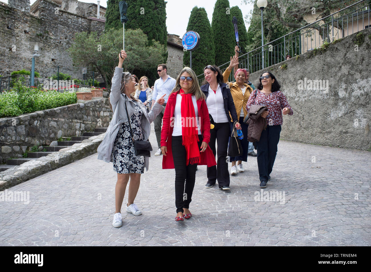 18 may 2019 - Sirmione, Lake Garda, Italy - Happy group of Brazilian tourist, walking with a tour guide - Stock Image