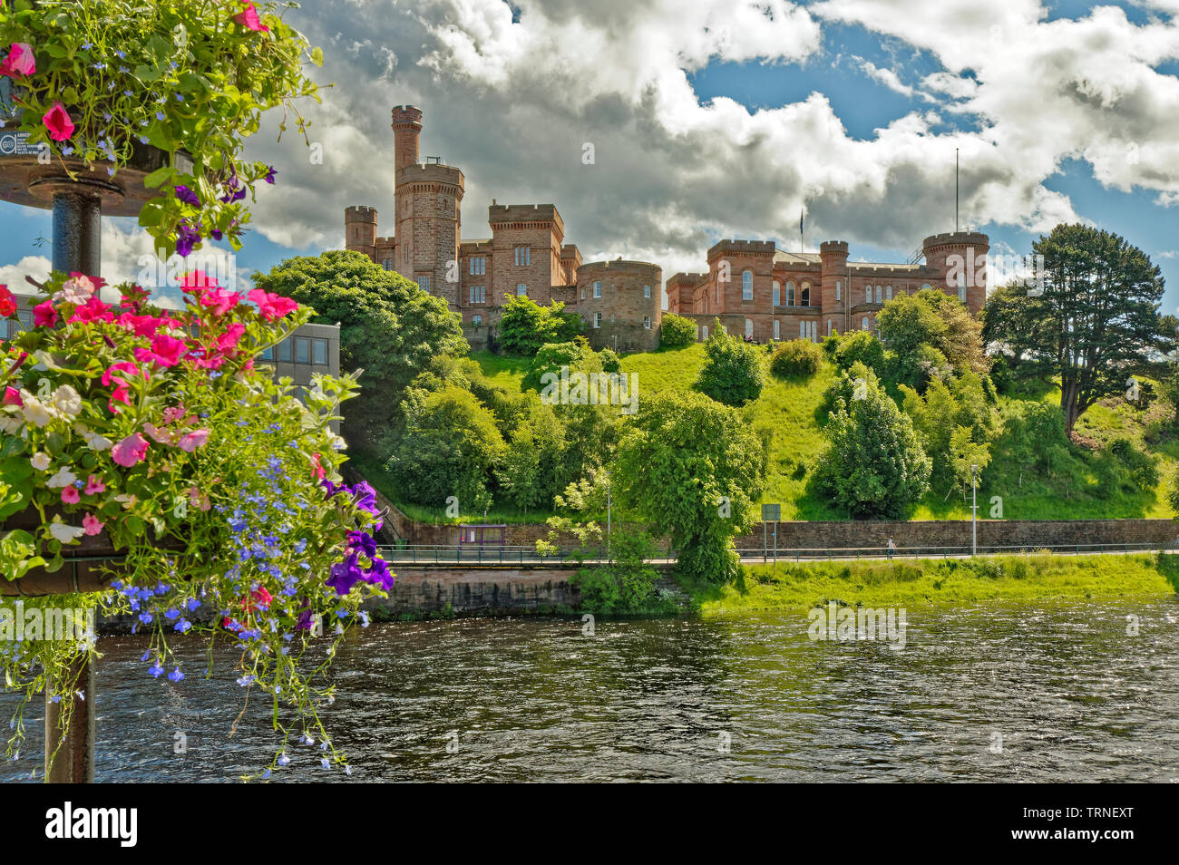 INVERNESS CITY SCOTLAND THE CASTLE AND VIEW OVER RIVER NESS FROM NESS ROAD BRIDGE WITH HANGING BASKETS AND PETUNIA FLOWERS - Stock Image