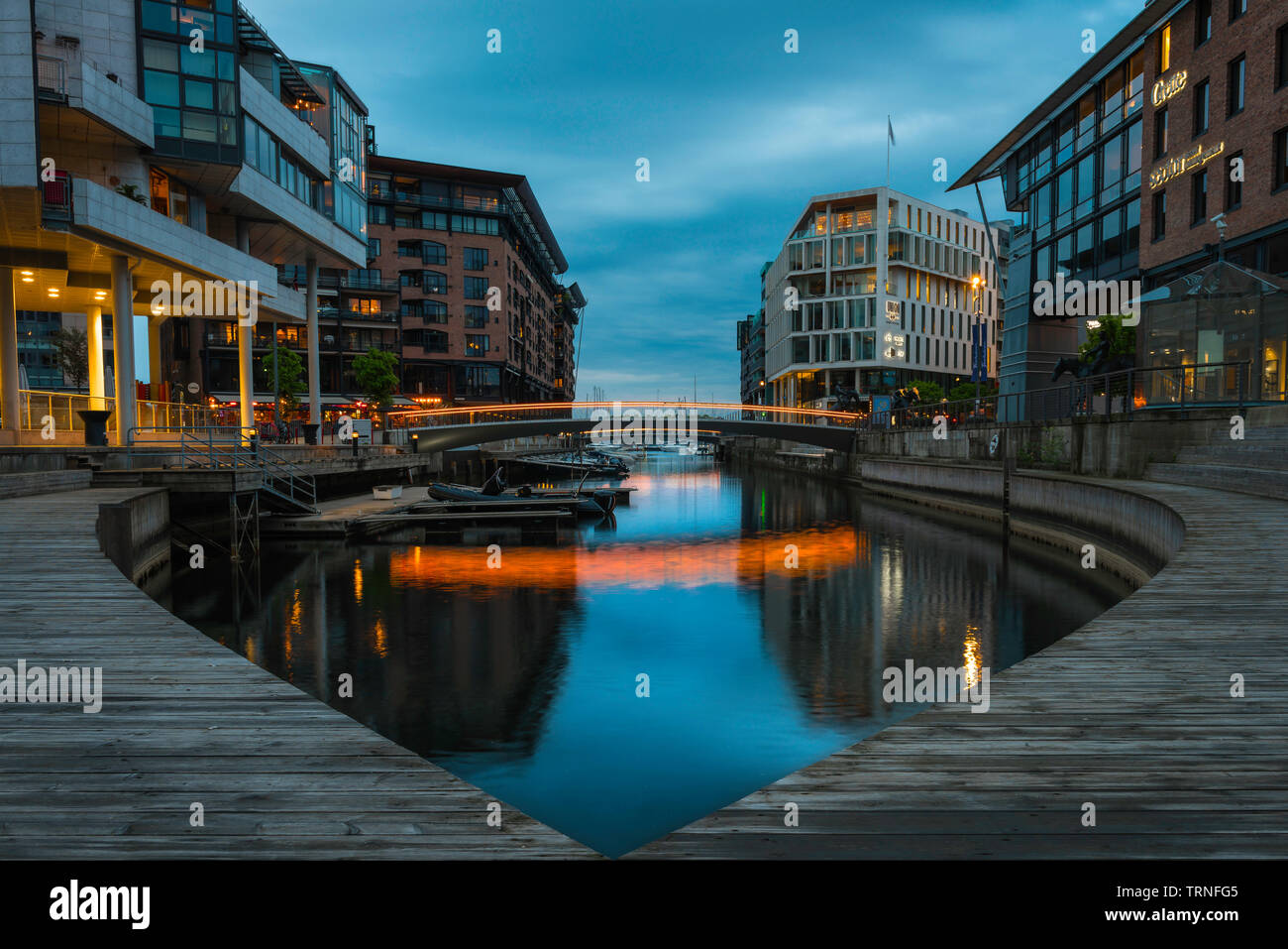 Aker Brygge Oslo, view at dusk of the harbour inlet inside the newly developed area of the Aker Brygge harbour district in Oslo, Norway. Stock Photo