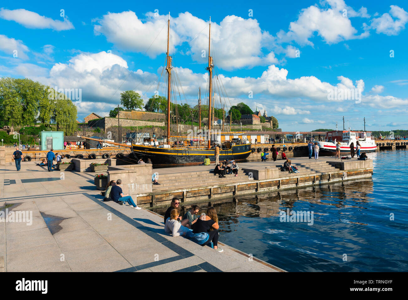 Oslo Norway, view of young people relaxing beside a quay in the harbour area (Aker Brygge) in Oslo on a summer afternoon, Norway. Stock Photo