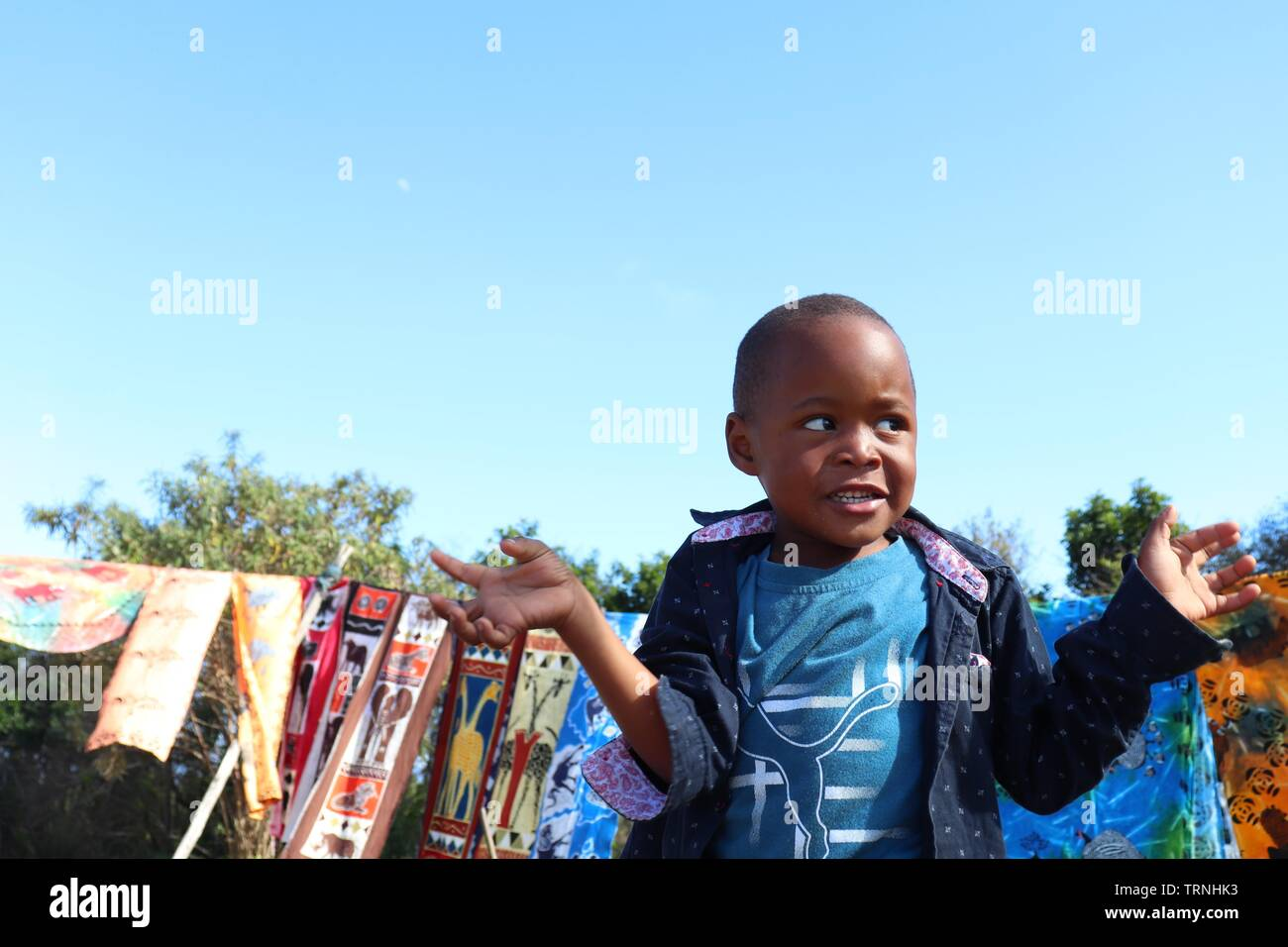 A little boy is playing while his parents sell souvenirs somewhere in South Africa - Stock Image