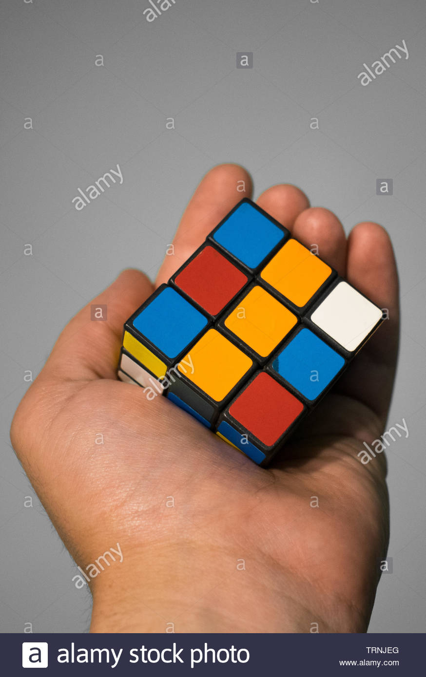 Rubber cube held in hand. - Stock Image