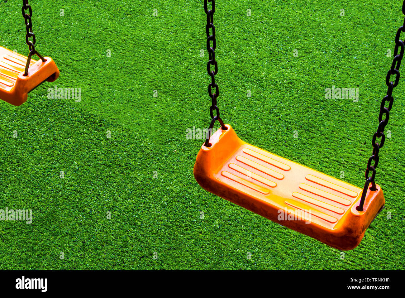 Double vivid orange color Swing seat on the artificial grass school yard - Stock Image