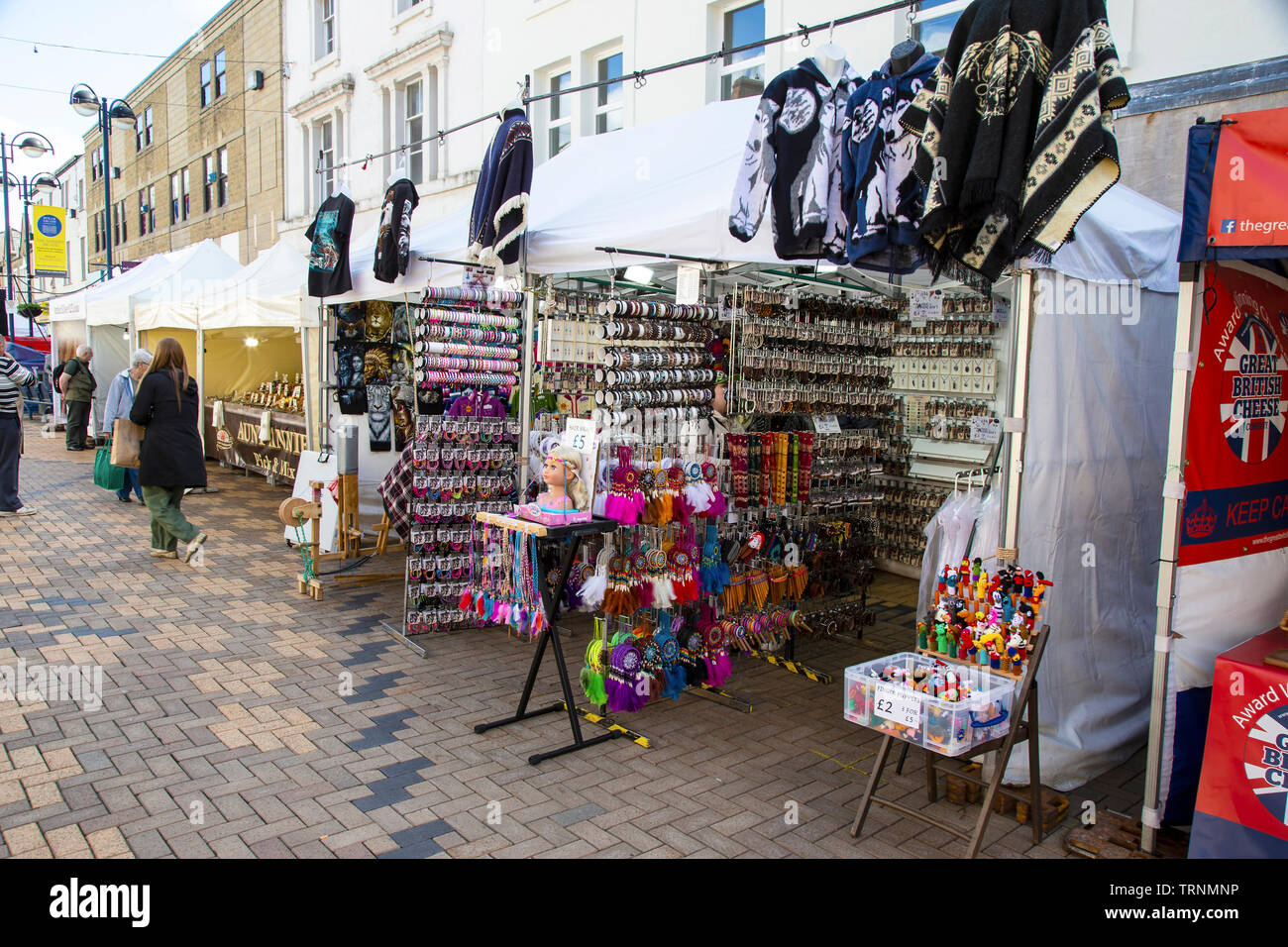 Open street market stall selling trinkets,  jewellery, bangles, adornments and bracelets during an International Street market event in West Yorkshire - Stock Image