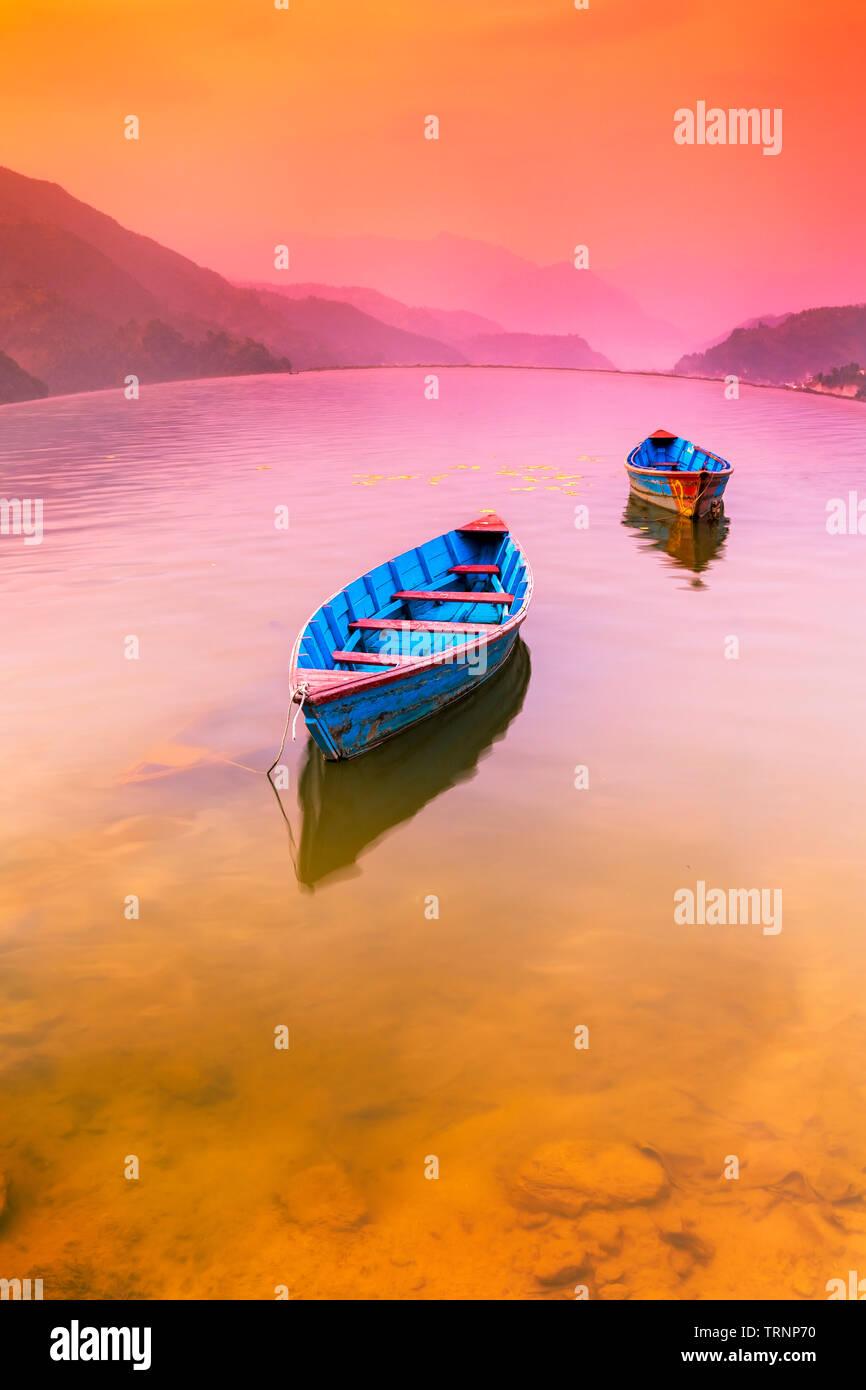 Two Boats parking in Phewa Lake,and Colorful Sunset On Background.Pokhara Nepal Stock Photo