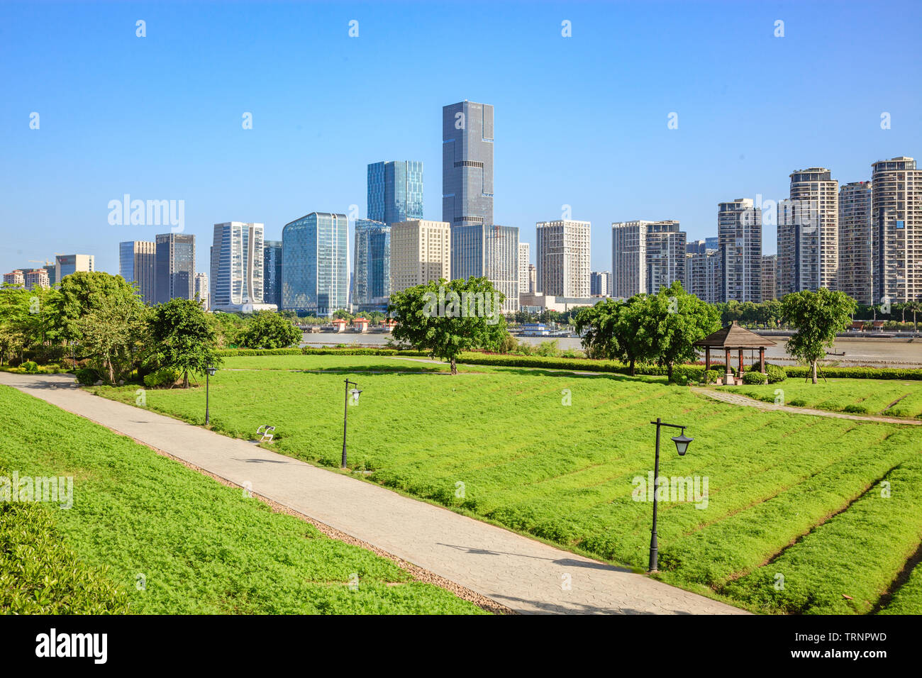 Cityscape and skyline of Fuzhou,viewed from green field in park,Fuzhou,China - Stock Image