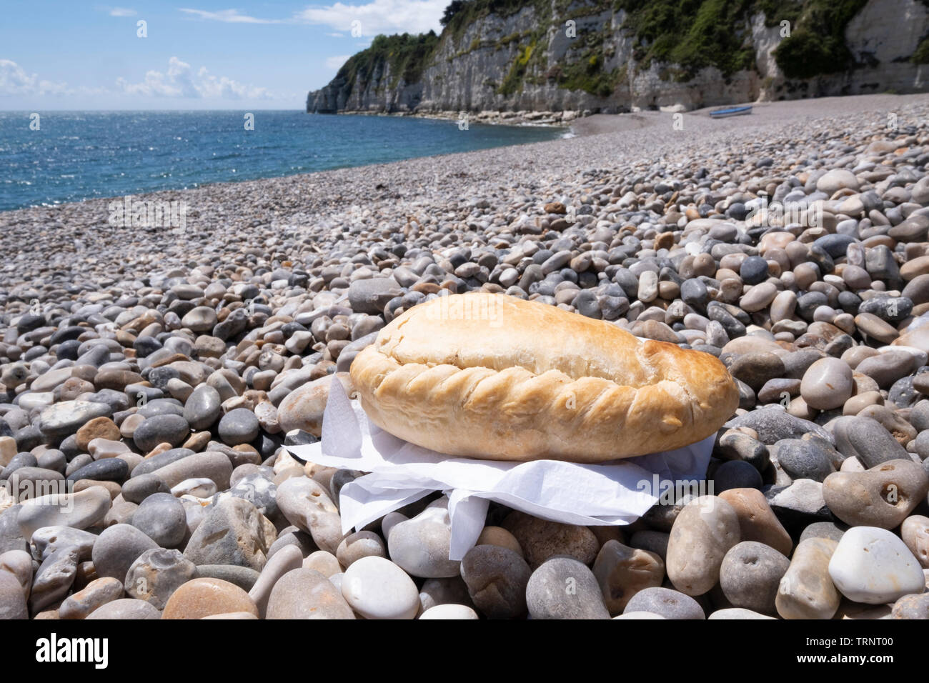 Cornish pasty on shingle beach with sea in background Stock Photo