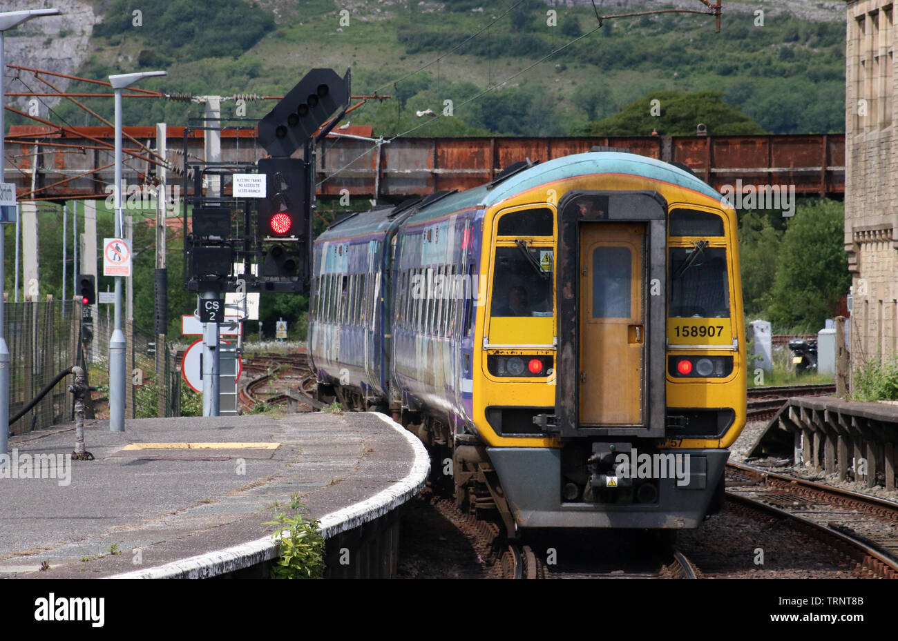 Two car class 158 express sprinter dmu in Northern livery leaving platform 2 at Carnforth railway station with passenger train Monday 10th June 2019. - Stock Image