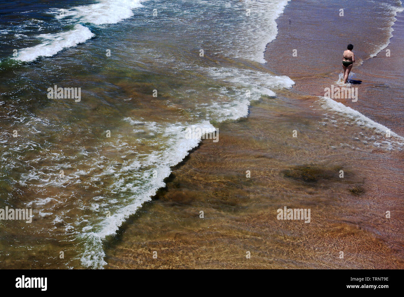 Woman wading in the sea looking at her her smartphone. - Stock Image