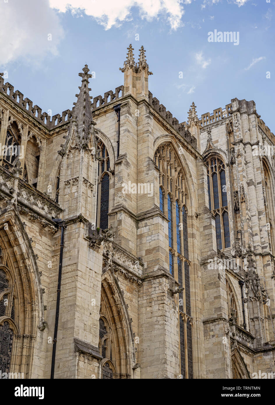 A section of York Minster with its medieval gothic architecture and central tower.  A cloudy sky is above. - Stock Image