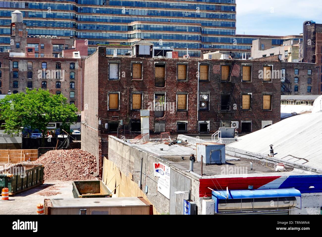Old brick red buildings in the process of being demolished or renovated, West side of New York City, NY, USA - Stock Image