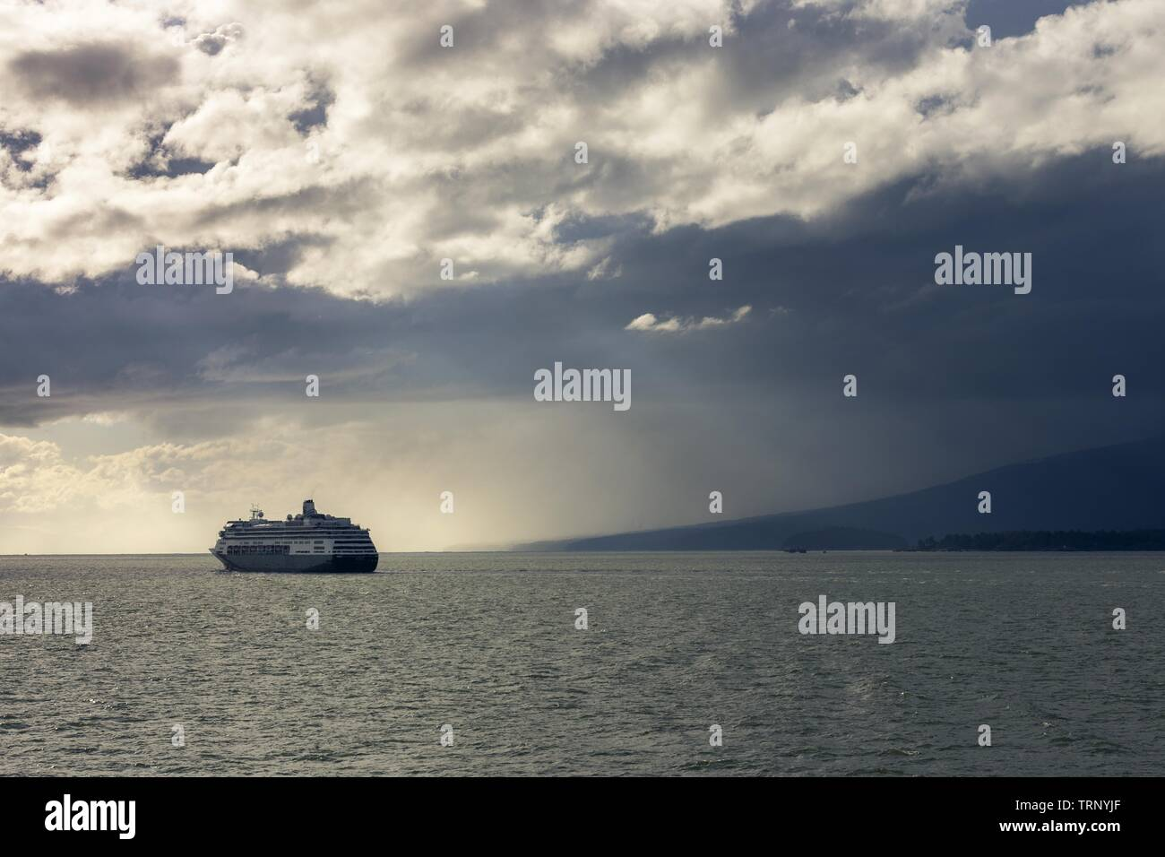 Large Cruise Liner Ocean Ship crossing Burrard Strait. Dramatic Stormy Sky on the Horizon off the Coast of Vancouver Island, British Columbia Canada Stock Photo