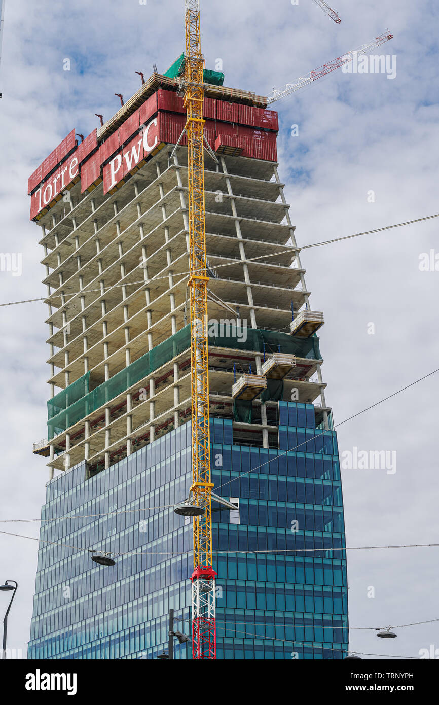 Il Curvo PwC Tower CityLife construction Milan, Italy. Low angle day view of Libeskind glass Tower The Curved One, part of Piazza Tre Torri CityLife. - Stock Image