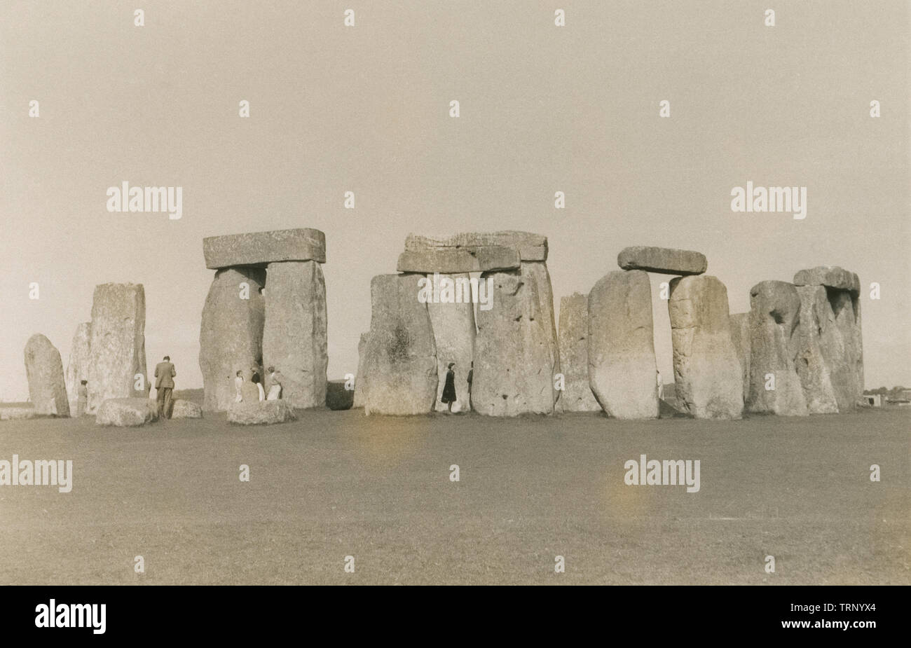 Antique c1950 photograph, tourists at Stonehenge in Wiltshire, England. Stonehenge is a prehistoric monument. It consists of a ring of standing stones set within earthworks in the middle of the most dense complex of Neolithic and Bronze Age monuments in England. SOURCE: ORIGINAL. PHOTOGRAPH - Stock Image