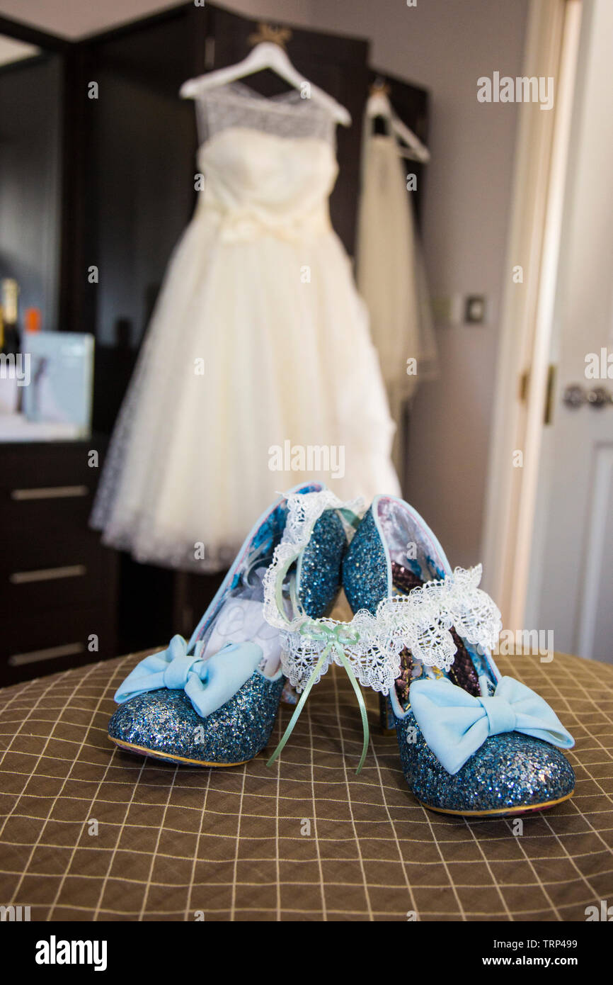 Brides Wedding Dress Hanging Up With Shoes And Flowers At The