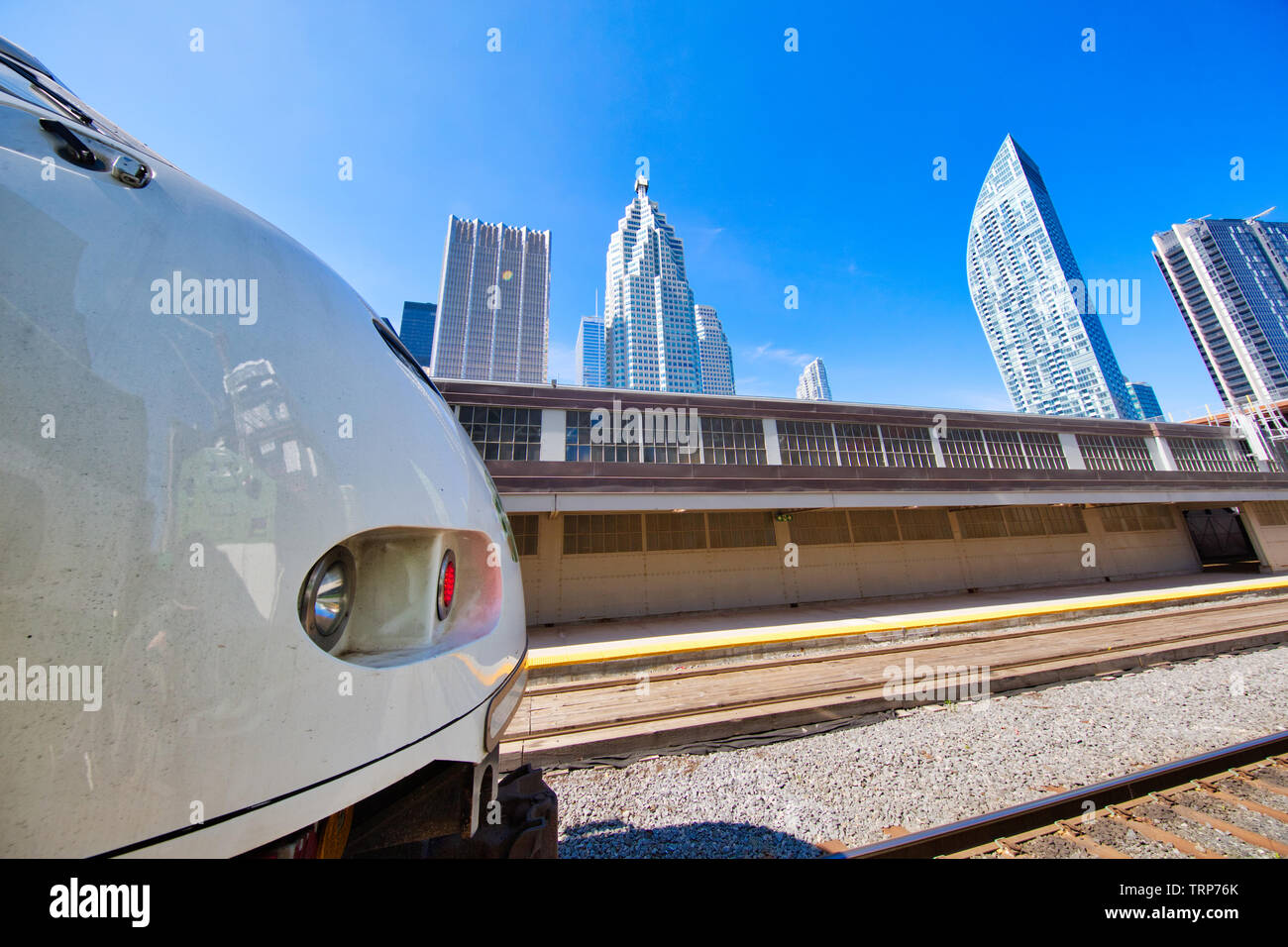 Toronto Go Train arriving at a platform at Union station terminal - Stock Image