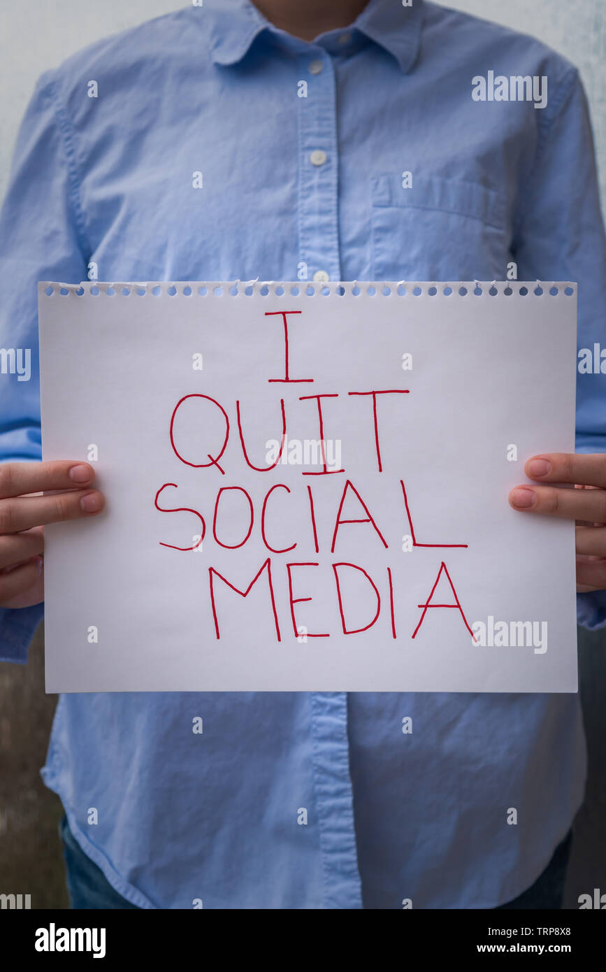 Person holding sign that says I Quit Social Media, illustrating the growing distrust in social media platforms - Stock Image