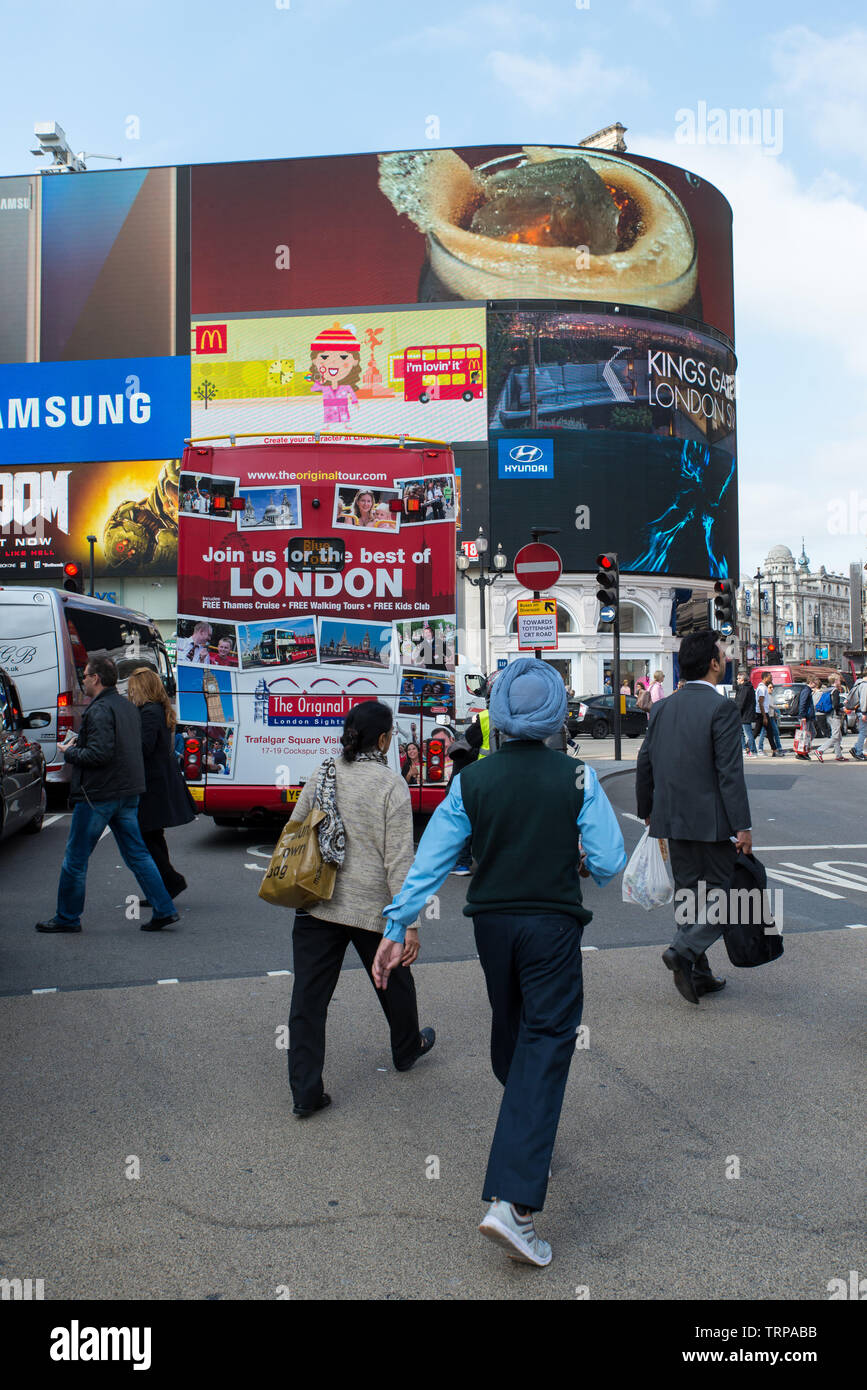 People from various communities cross path at Piccadilly Circus, London. Stock Photo