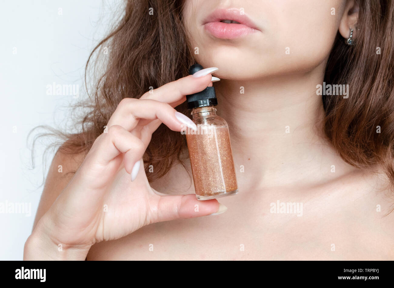 young beautiful curly woman uses gold serum for face on white background. The concept of facial skin care. Stock Photo