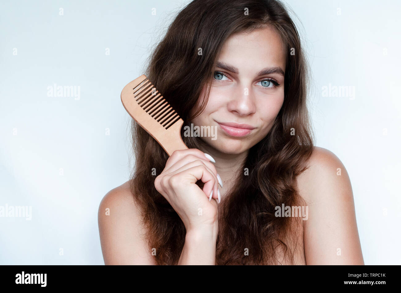 young beautiful woman uses a wooden  crest for curly hair Stock Photo