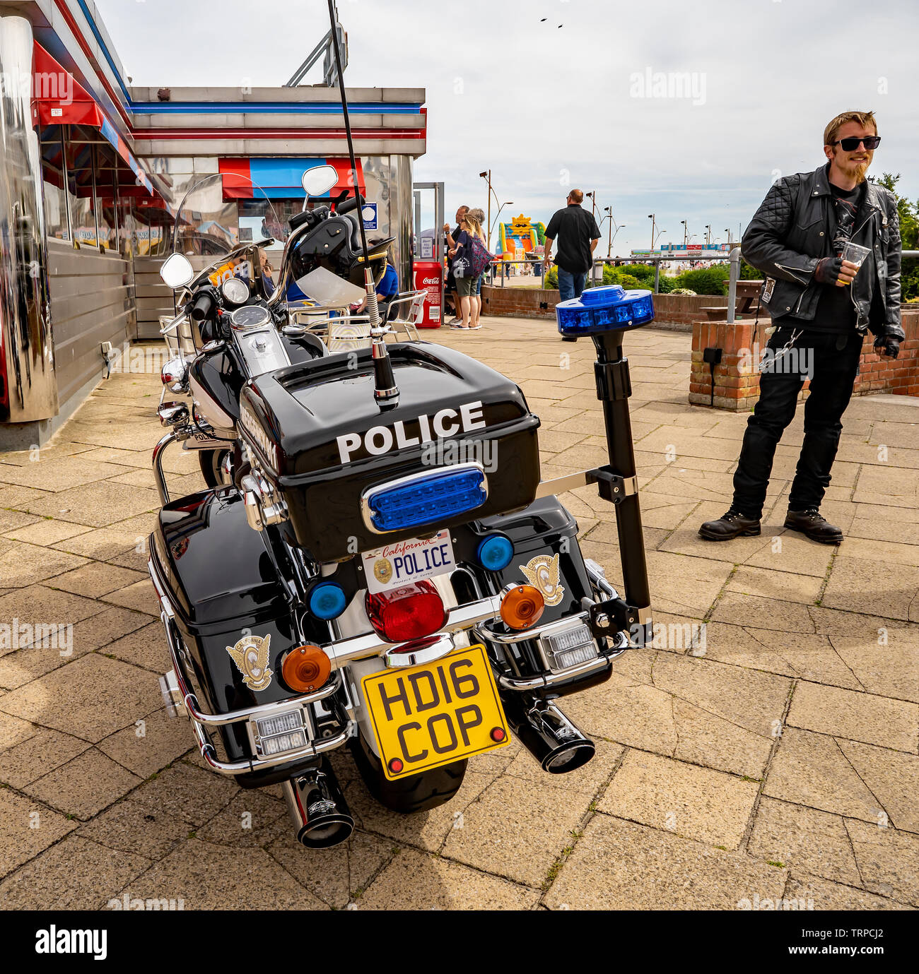 Harley Davidson customized to look like a replica US police motorcycle parked outside the American diner in the seaside town of Great Yarmouth - Stock Image