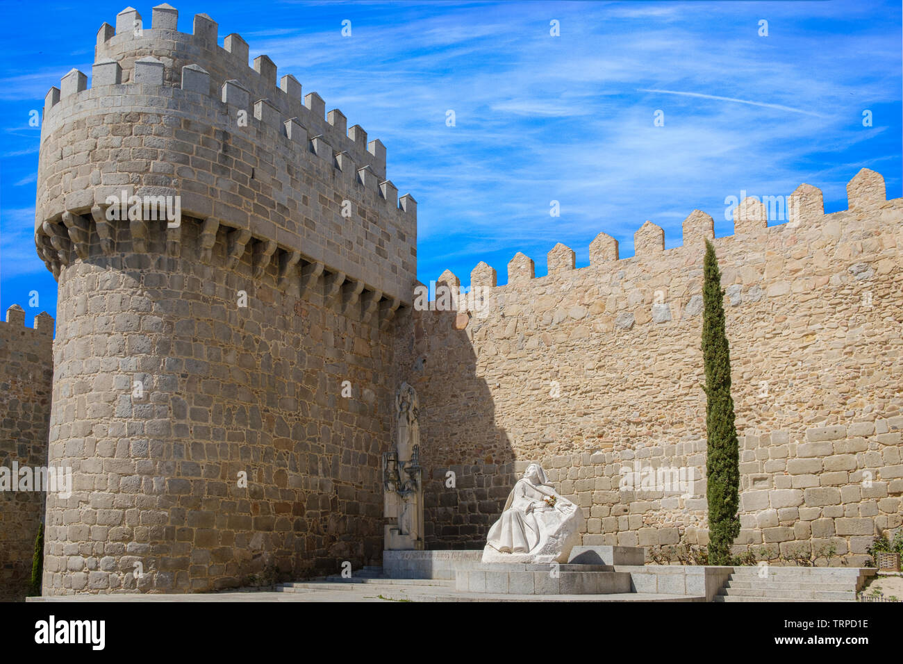 Walls surrounding Spanish city of Avila, with Santa Teresa sculpture - Stock Image