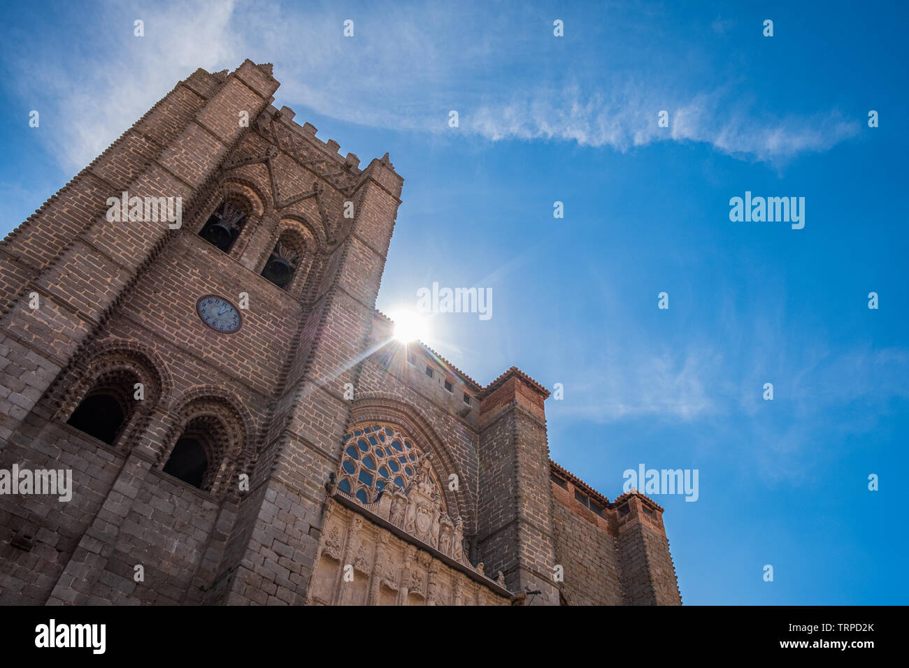 Main view of Cathedral of Avila, Spain, with sun and clouds in a blue sky - Stock Image