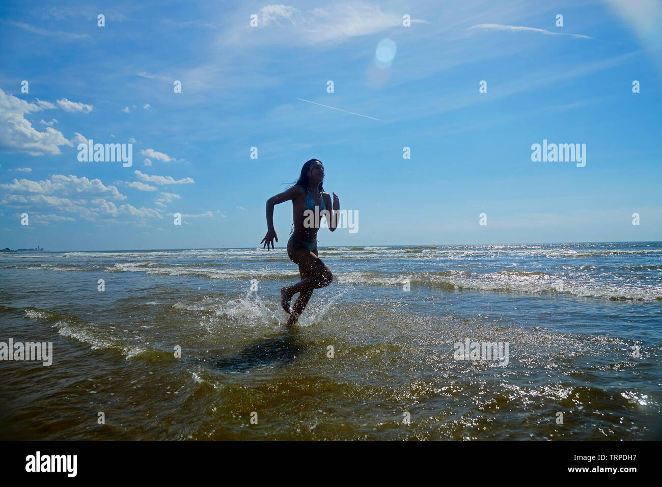 Young Asian girl in swimwear running and splashing in the ocean on a hot day in bright summer sunshine - Stock Image