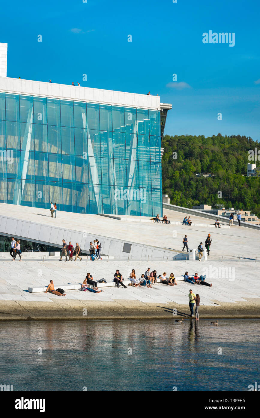 Opera House Oslo, waterfront view in summer of people sunbathing or walking on the vast access ramp leading to the roof of the Oslo Opera House. Stock Photo