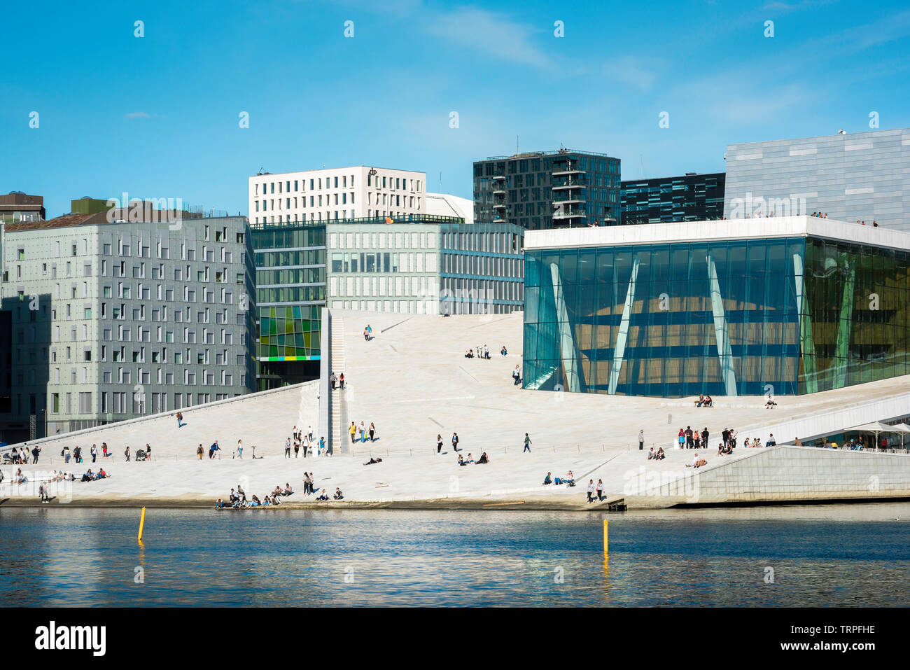 Opera House Oslo, view across the fjord of people on the vast access ramp leading to the roof of the Oslo Opera House, with Barcode Buildings beyond. Stock Photo