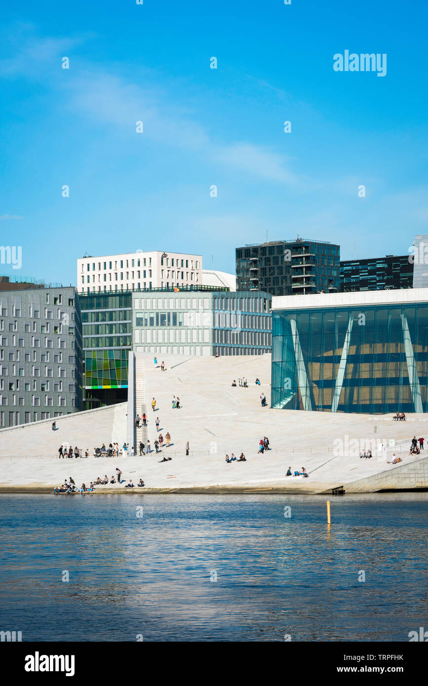 Oslo Opera House, view across the fjord of people on the vast access ramp leading to the roof of the Oslo Opera House, with Barcode Buildings beyond. Stock Photo
