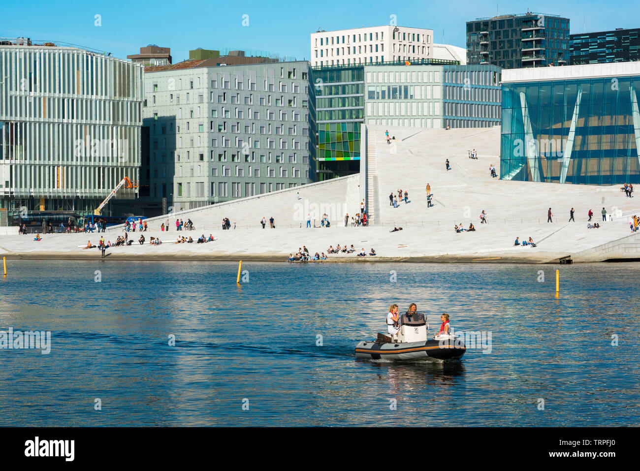 Oslo Norway, view of young people sailing a boat past the Oslo Opera House and the city's Barcode district on a summer afternoon, Norway. Stock Photo