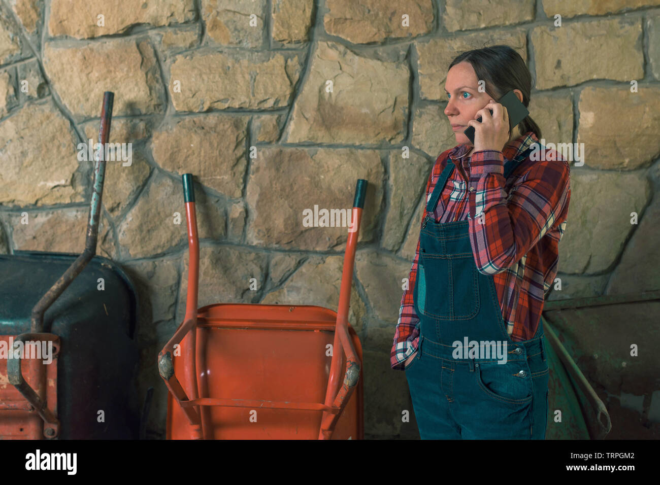 Worried female farmer talking on mobile phone in the stable. Adult woman in plaid shirt and denim overall trousers in telephone conversation. - Stock Image