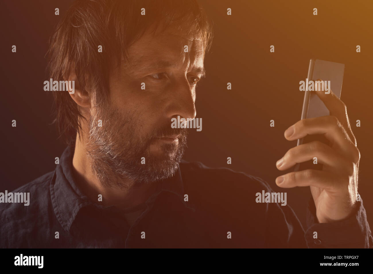 Adult man looking at mobile phone screen. Portrait of caucasian male with beard using modern smartphone. Stock Photo