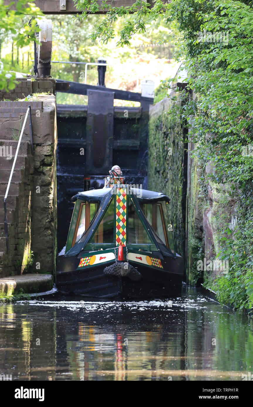 Portrait, front view of isolated UK narrow boat exiting canal lock on a sunny morning, steered by isolated female at rear of canal boat. - Stock Image