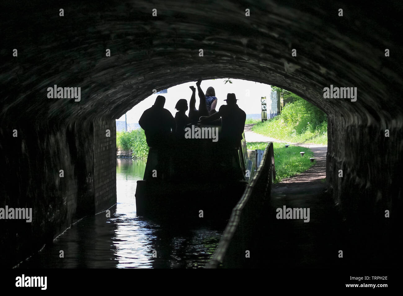Silhouetted rear view of people in UK narrowboat on British canal moving through dark tunnel; upside down man, legs in air, propels boat by legging. Stock Photo