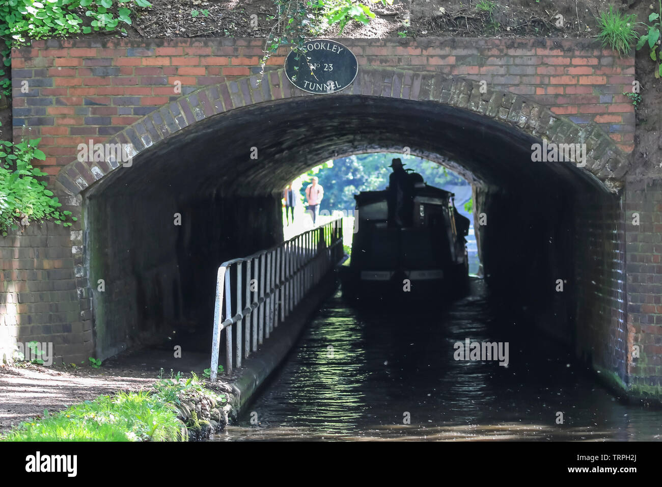 Silhouetted rear view of narrowboat on a UK canal moving away through a dark canal tunnel; people on towpath watching at other end in bright sunlight. Stock Photo