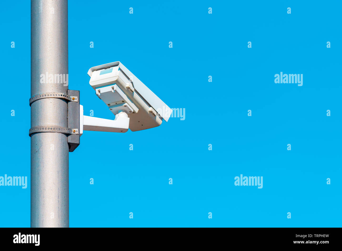 Traffic surveillance camera mounted on the post with large portion of blue sky as copy space Stock Photo