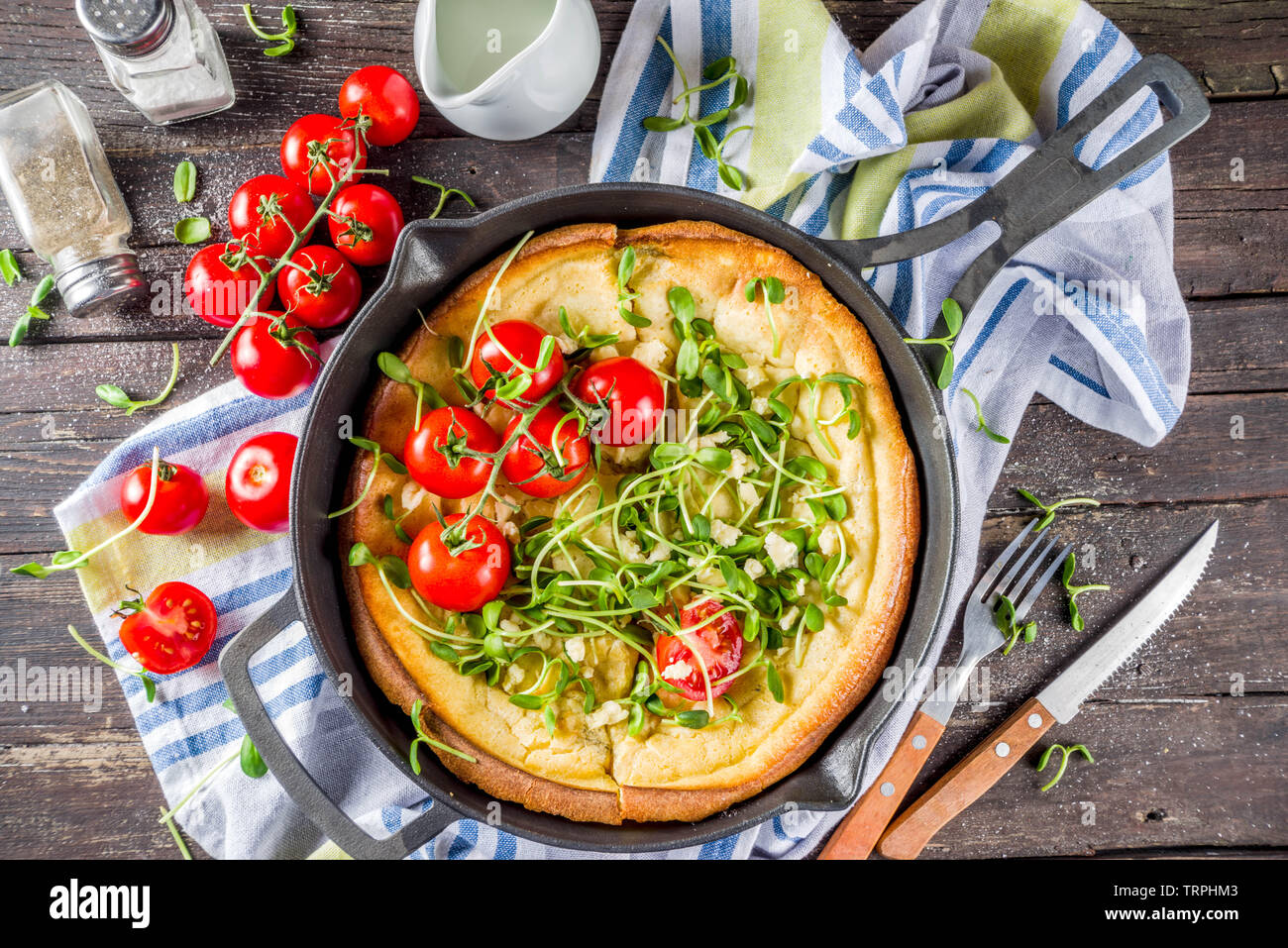 Savory vegan dutch baby baked pancake with salad leaves and vegetables, wooden background copy space - Stock Image