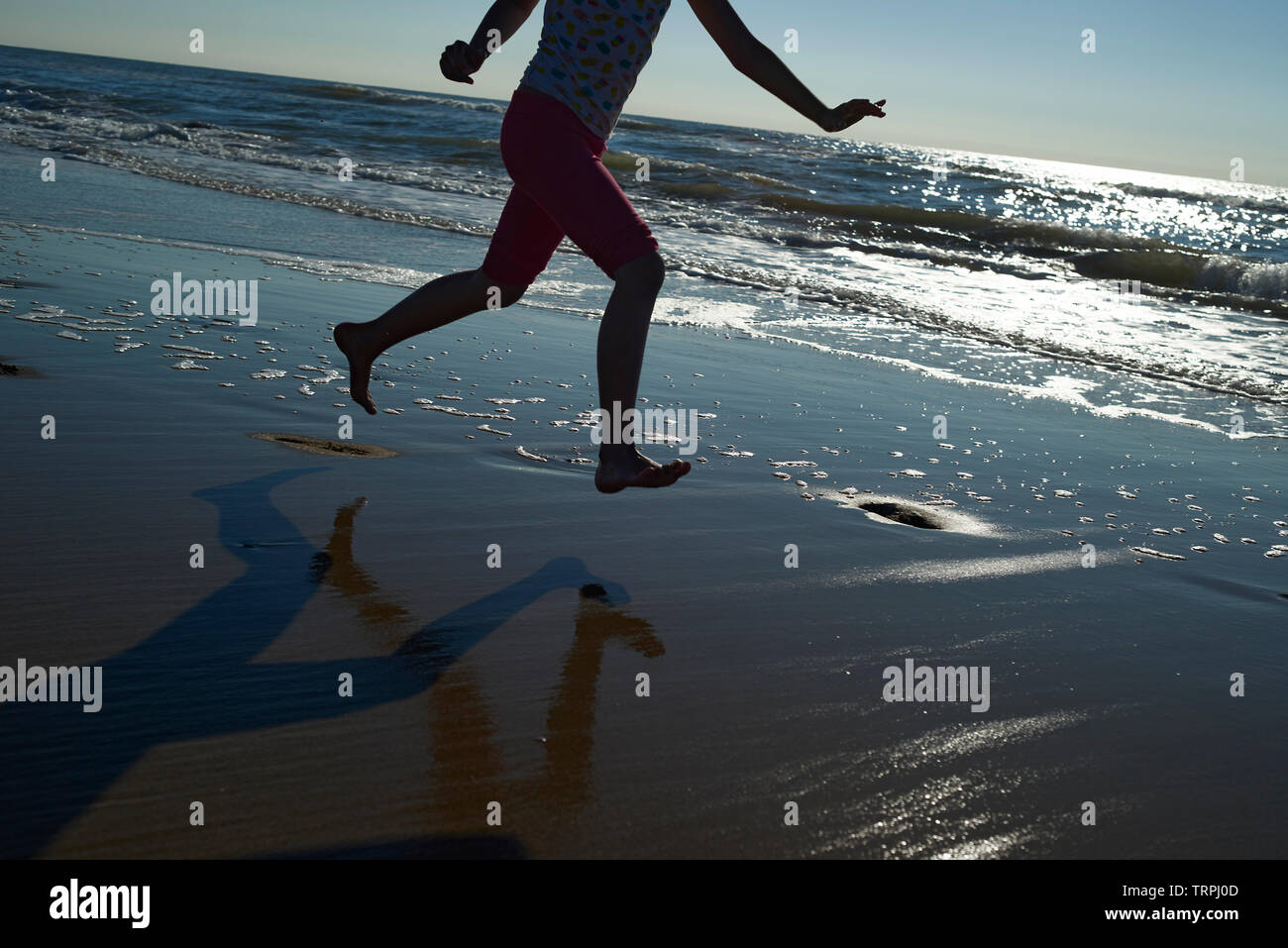Asian girl in swimwear running and splashing in the ocean on a hot day in bright summer sunshine - Stock Image