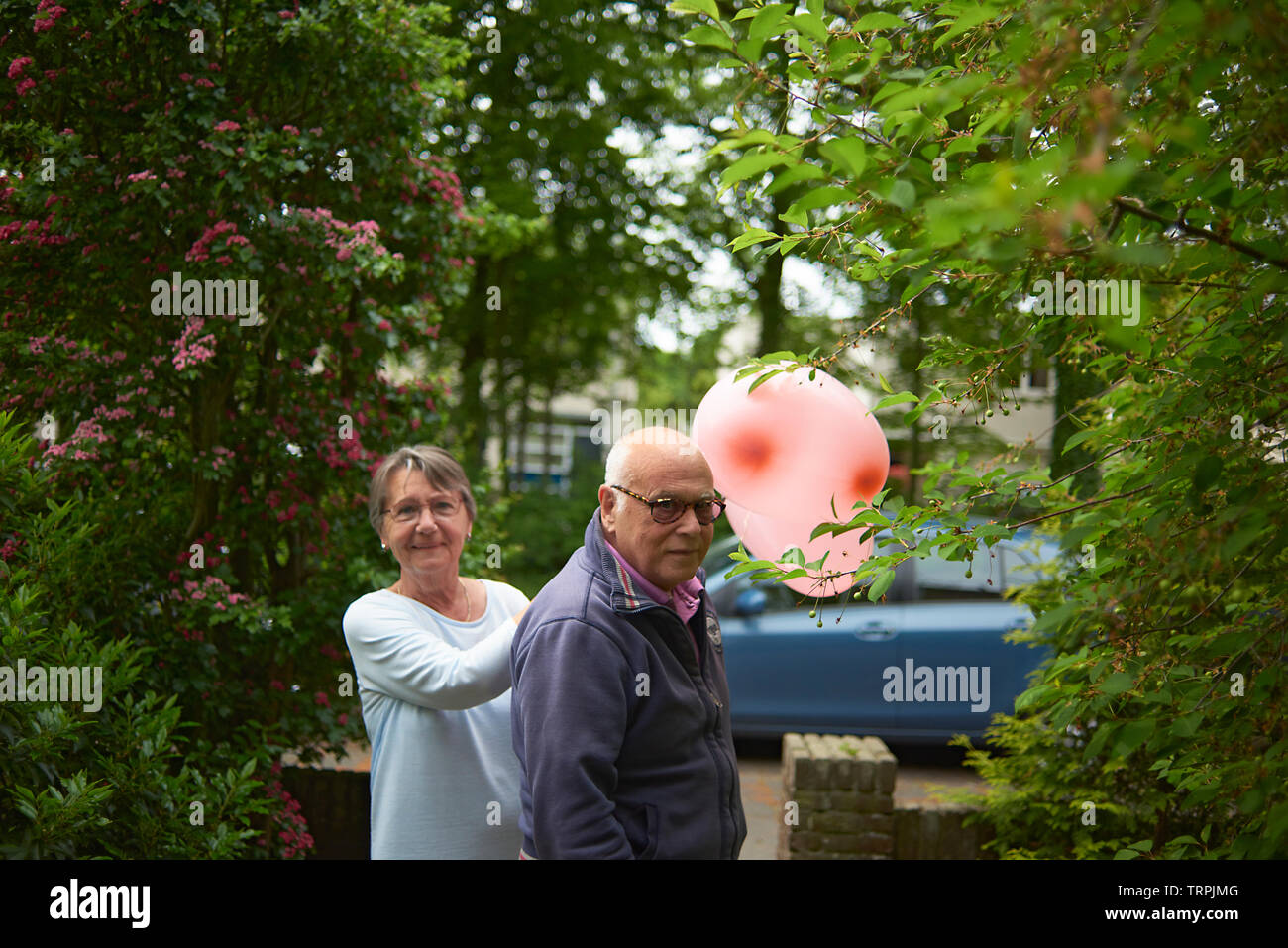 Grandparents in their front garden holding a large heart shaped balloon on their way out - Stock Image