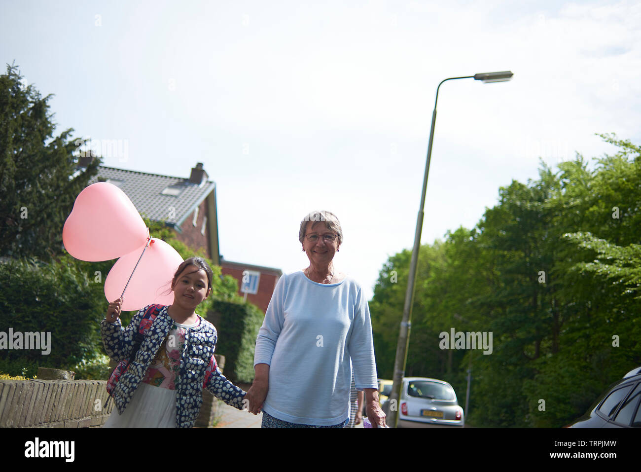 Grandmother walking down the street with their grand daughter who is holding a large heart shaped balloon on her birthday - Stock Image
