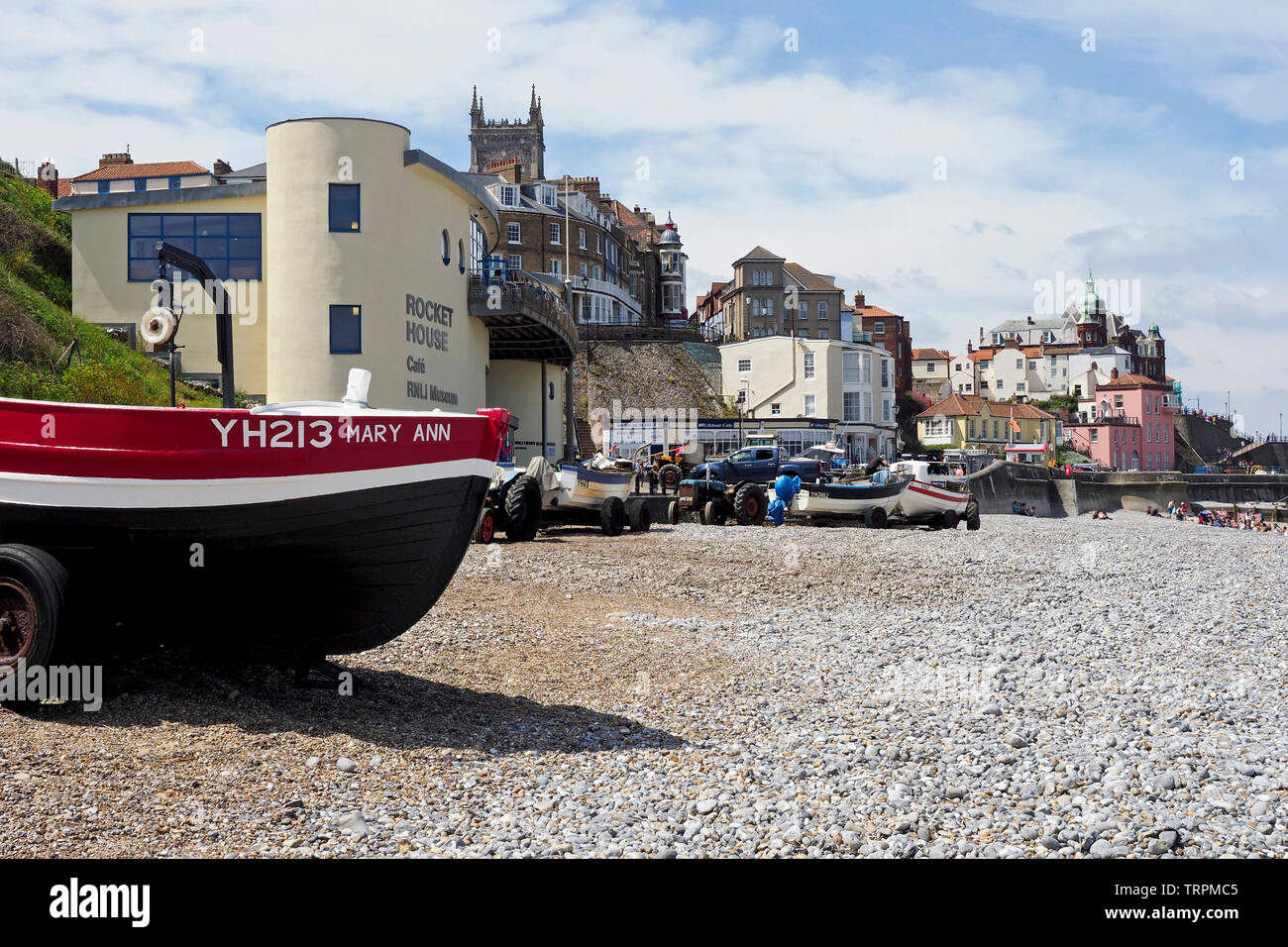 Fishing boats on the shingle beach in Cromer,Norfolk with the historic holiday resort town and picturesque promenade in the background. Stock Photo
