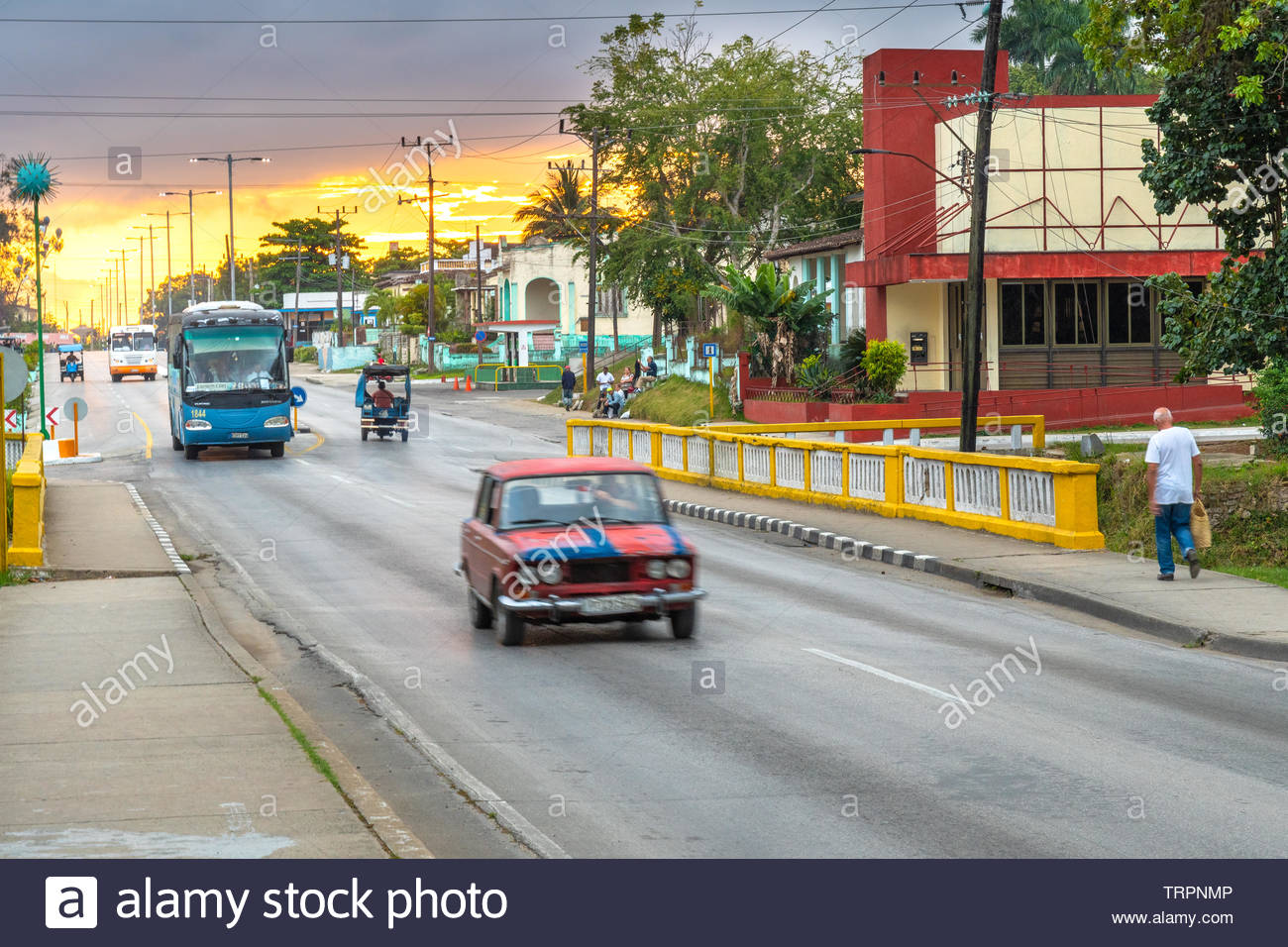 A red LADA car driving in the morning. There is a dramatic-sky sunrise in the Central Road which traverse the city from one point to the other. There Stock Photo